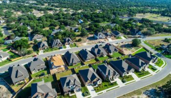 Aerial drone view above suburb homes curved road into suburban community