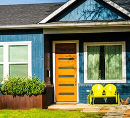 modern wood door with yellow retro glider on patio porch Real estate modern homes modern day living in Austin Texas suburb neighborhood