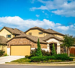 Real estate suburb development in Austin Texas nice new builds community neighborhood in new suburbia homes and houses with two car garage and nice trees and landscaping