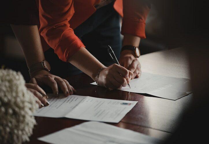 2 people signing paperwork